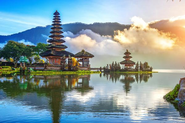 A lakeside view of temples and greenery in Bali, which can be visited with a cheap holiday package from Flight Centre.