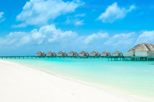A view of a beach and overwater bungalows in the Maldives, which can be visited with a cheap holiday package from Flight Centre.