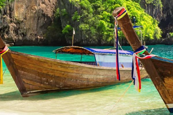 A view of two boats on a beach in Krabi, which can be visited with a cheap holiday package from Flight Centre.